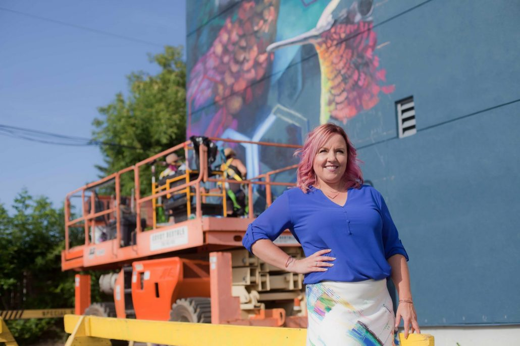 Erin Stevenson standing in front of a colourful mural comprised of two hummingbirds