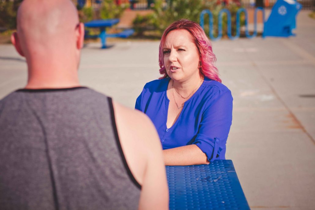 Erin Stevenson speaking with a local resident at Jubilee Park. Sitting at picnic table discussing.